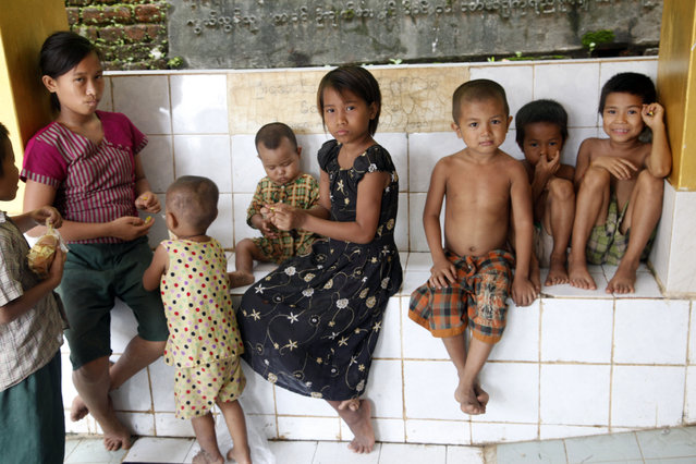 Children watch as they stay at a monastery, opened as a temporary relief camp, in Myauk U, Rakhine State, western Myanmar, Tuesday, August 4, 2015. New devastation is feared in Myanmar as water from the badly flooded central and northern regions flows down rivers to the country's more populous areas. Officials say the death toll from weeks of almost continuous rain is 46, with more than 200,000 people affected by flooding in 11 of the country's 14 states and divisions. (Photo by Khin Maung Win/AP Photo)