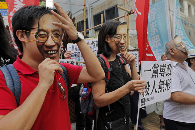 Protesters wear masks of jailed Chinese Nobel Peace laureate Liu Xiaobo during a demonstration outside the Chinese liaison office in Hong Kong, Tuesday, June 27, 2017. Liu Xiaobo has been released on medical parole after being diagnosed with late-stage liver cancer, his lawyer said Monday. (Photo by Vincent Yu/AP Photo)