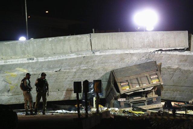 A vehicle is trapped underneath a bridge that collapsed while under construction in Belo Horizonte, July 3, 2014. The unfinished overpass collapsed in the Brazilian World Cup host city of Belo Horizonte on Thursday, killing at least one person and casting a shadow over a tournament that has suffered repeated construction accidents and delays. (Photo by Ivan Alvarado/Reuters)