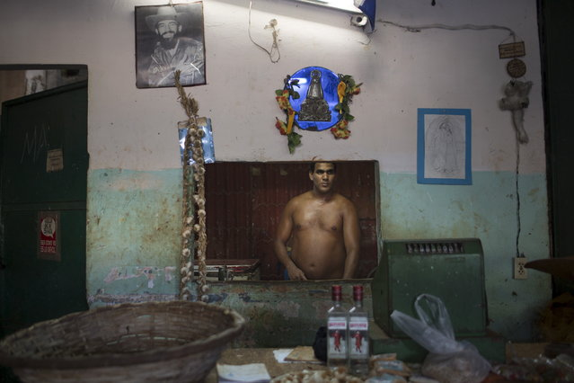 A photograph of Cuba's late rebel revolutionary Camilo Cienfuegos decorates a wall inside a state run market as Osmani Aguilar, 39, waits for customers in Havana, July 20, 2015. (Photo by Alexandre Meneghini/Reuters)