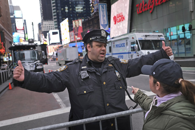 A police officer directs pedestrians through Times Square in New York on New Year's Eve, Tuesday, December 31, 2019. Revelers around the globe are bidding farewell to a decade that will be remembered for the rise of social media, the Arab Spring, the #MeToo movement and, of course, President Donald Trump. (Photo by Seth Wenig/AP Photo)