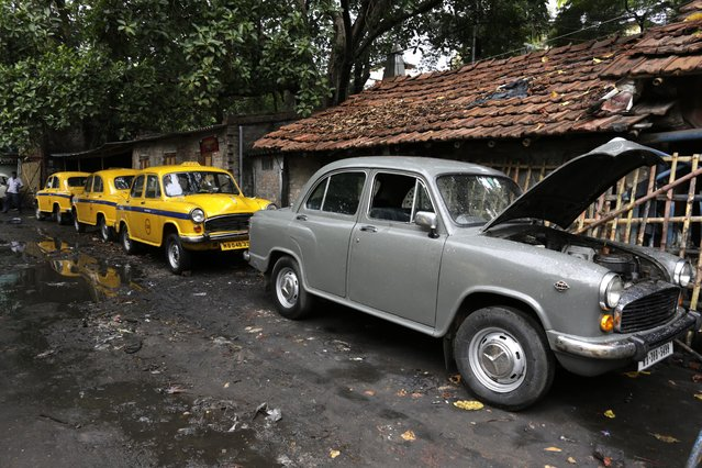 Ambassador cars, both taxis, in yellow and one private, are parked near a workshop for repairs in Kolkata, india, Monday, May 26, 2014. (Photo by Bikas Das/AP Photo)