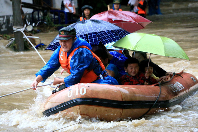 A rescuer grabs a rope to prevent a raft carrying residents from being flushed away as residents are evacuated from a flooded area in Jiujiang, Jiangxi Province, China, June 19, 2016. (Photo by Reuters/Stringer)
