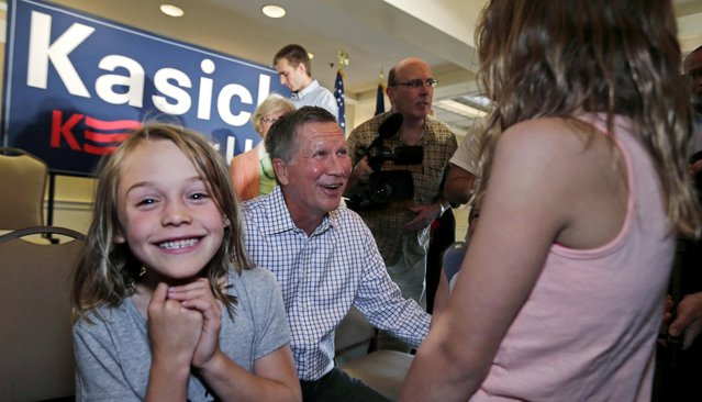 Carolyn Milks, 6, of Greenland, N.H., smiles as she meets Republican presidential candidate Ohio Gov. John Kasich with her sisters following a town hall style gathering during a campaign stop in Greenland, Wednesday, July 22, 2015. (Photo by Charles Krupa/AP Photo)