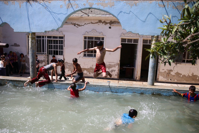 Boys swim to cool down from heat inside a swimming pool, in the rebel held besieged town of Douma, eastern Damascus suburb of Ghouta, Syria, June 23, 2016. (Photo by Bassam Khabieh/Reuters)