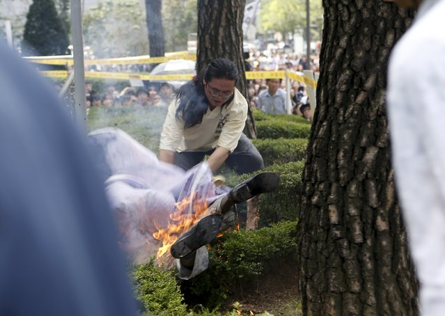 A man attempts to put out flames from another man (bottom) who set himself on fire during a weekly anti-Japan rally to demand for an official apology and compensation from the Japanese government in front of the Japanese embassy in Seoul, South Korea, August 12, 2015. (Photo by Kim Hong-Ji/Reuters)
