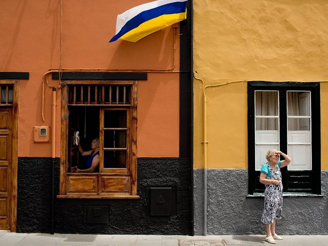 A woma cleans her window as her neighbour looks on hours before of Virgen del Carmen procession in Puerto de la Cruz on the Canary island of Tenerife. (Photo by Gonzalo Arroyo Moreno/Getty Images)