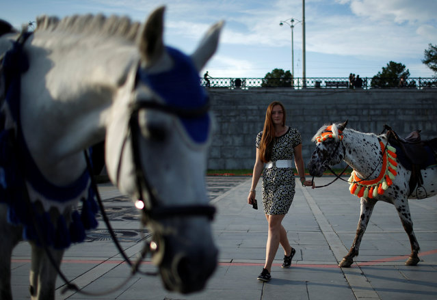 A woman leads a horse for tourists attraction in Yekaterinburg, Russia, July 28, 2017. (Photo by David Mdzinarishvili/Reuters)