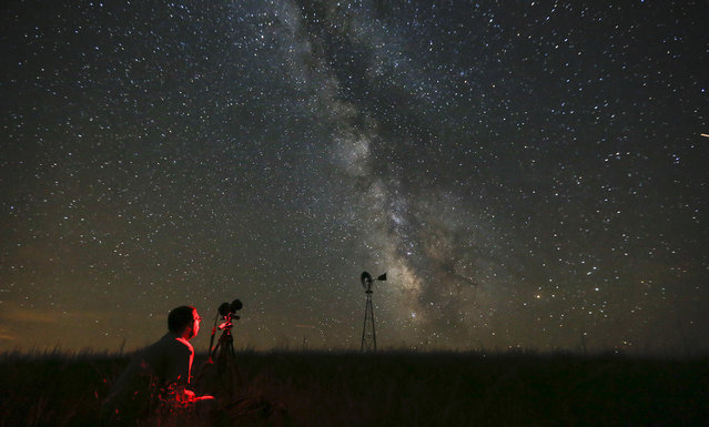 Omaha photographer Lane Hickenbottom photographs the night sky in a pasture near Callaway, Neb. on Wednesday night, July 23, 2014. With no moon in the sky, the Milky Way was visible to the naked eye. (Photo by Travis Heying/AP Photo/The Wichita Eagle)