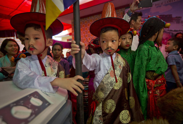 Tibetans children watch others dance as they wait for their turn to perform during celebrations marking the 82nd birthday of their spiritual leader the Dalai Lama at a Tibetan settlement in New Delhi, India, Thursday, July 6, 2017. Thousands belonging to Tibetan community waved white scarves and banners, lit incense and prayed for the Dalai Lama's long life as he turned 82 on Thursday. The Dalai Lama is currently visiting the Jokhang Gonpa, a Buddhist monastery, built in Ladakh in the Indian portion of Kashmir. (Photo by Manish Swarup/AP Photo)