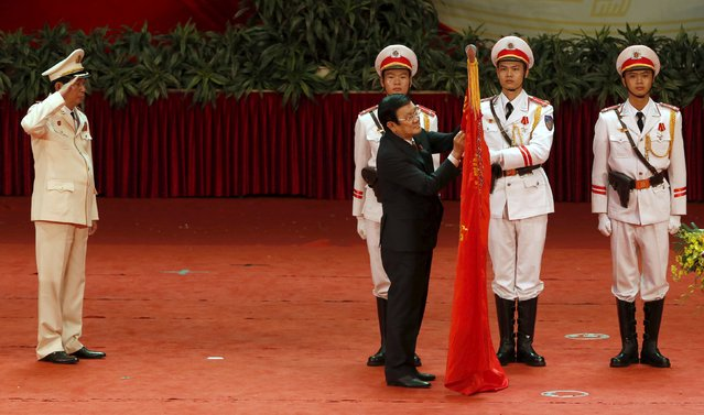 Vietnam's Public Security (Police) Minister General Tran Dai Quang (L) salutes as President Truong Tan Sang presents Golden Star medals on a police flag during celebrations to commemorate the 70th anniversary of the establishment of the Vietnam Public Security police force at the National Convention Center in Hanoi August 18, 2015. (Photo by Reuters/Kham)