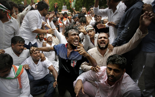 Supporters of India's opposition Congress party shout slogans as they get drenched after police used water cannon while trying to march towards the Indian parliament during a protest against the policies of Indian government in New Delhi, India, Thursday, August 10, 2017. (Photo by Altaf Qadri/AP Photo)