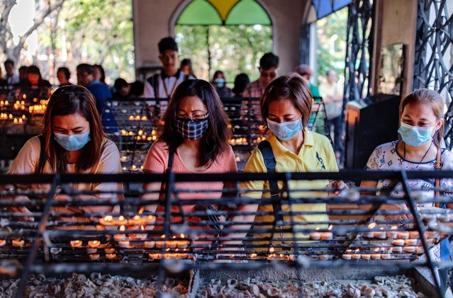 Filipino Catholics wearing protective masks light candles during Ash Wednesday services at a church on February 26, 2020 in Paranaque city, Metro Manila, Philippines. The Philippines Catholic Church has recommended sprinkling ash on the heads of devotees, rather than the usual practice of rubbing it on foreheads, to avoid physical contact as a precaution against COVID-19. The first COVID-19 death outside of China was reported in the Philippines last February 2, while the country has reported only 3 confirmed cases of the coronavirus so far. With over 78,000 confirmed cases around the world, the virus has so far claimed over 2,700 lives. (Photo by Ezra Acayan/Getty Images)