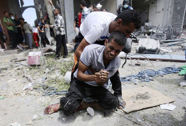 A Palestinian man reacts after the body of his mother was removed from under the rubble of their house which witnesses said was destroyed in an Israeli air strike, in Rafah in the southern Gaza Strip August 4, 2014. Palestinians accused Israel of breaking its own ceasefire on Monday by launching a bomb attack on a refugee camp in Gaza City that killed an eight-year-old girl and wounded 29 other people. An Israeli military spokeswoman said she was checking the report. (Photo by Ibraheem Abu Mustafa/Reuters)