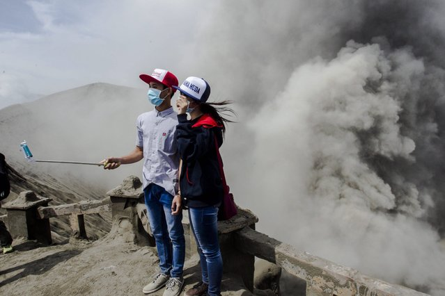 Locals take a picture as Mount Bromo spews ashes into the air during a volcanic eruption in Probolinggo, East Java, Indonesia, 13 July 2016. The Bromo volcano's ash was spit towards the East Java city Malang, resulting in the closure of Abdul Rachman Saleh Airport on 11 July 2016. (Photo by Fully Handoko/EPA)