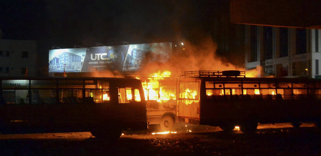 In this late Tuesday, August 25, 2015 photo, passenger buses set on fire by a mob go up in flames in Surat, Gujarat state, India. Authorities issued a curfew Tuesday night in at least five cities in Gujarat state, after mobs attacked police officers with stones and sticks and burned government and private vehicles. (Photo by Dinesh Trivedi/AP Photo)