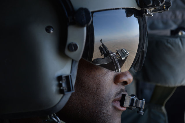 This photo taken on august 11, 2014 shows a US soldier, part of the NATO-led International Security Assistance Force (ISAF), manning a machine gun onboard a Chinook helicopter over the Gardez district of Paktia province. All NATO combat troops will be out of Afghanistan by the end of the year, though some US special forces are set to stay on to conduct discreet strikes against Al-Qaeda remanents. (Photo by Shah Marai/AFP Photo)
