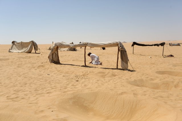 "A worker flattens the sand in the area of a tent before patients use it as a ""sauna"" after their sand bath in Siwa, Egypt, August 12, 2015. (Photo by Asmaa Waguih/Reuters)"
