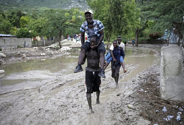 Men carry others, so they do not soil their shoes and clothes, through a mudslide caused by Tropical Storm Erika in Carries, Haiti, August 29, 2015. (Photo by Andres Martinez Casares/Reuters)