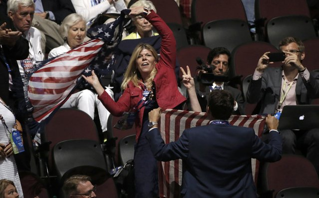 Supporters of Republican U.S. presidential nominee Donald Trump obscure a protester from the activist group Code Pink holding an anti-racism and anti-hate banner, so that only her hand (R) making a peace sign can be seen as she interrupts the proceedings at the Republican National Convention in Cleveland, Ohio, U.S. July 19, 2016. (Photo by Mike Segar/Reuters)