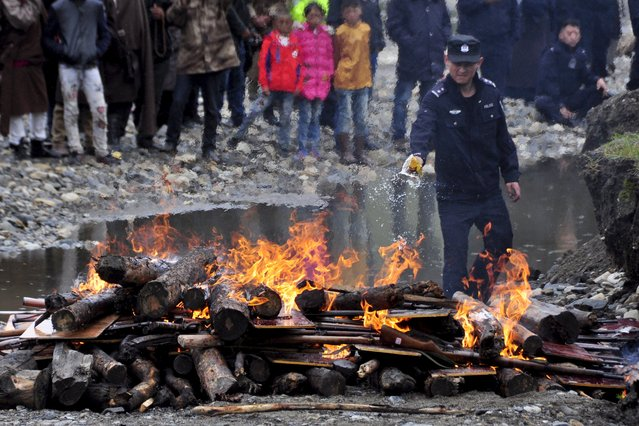 A policeman burns illegal weapons confiscated by authorities during a massive destruction event in Garze Tibetan Autonomous Prefecture, Sichuan province, China, September 1, 2015. (Photo by Reuters/Stringer)