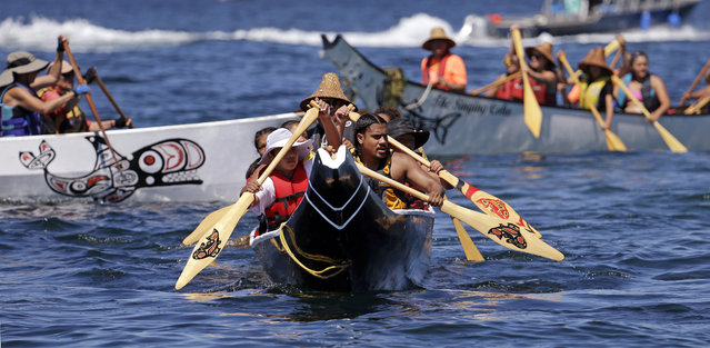 A canoe from the Puyallup Tribe is paddled toward a landing during an annual journey Wednesday, July 27, 2016, in Seattle. Dozens of tribal canoes were arriving at Alki Beach in Seattle as part of an annual Native American celebration. Members of the Muckleshoot Tribe greeted the boats Wednesday afternoon as part of the 2016 Paddle to Nisqually. (Photo by Elaine Thompson/AP Photo)
