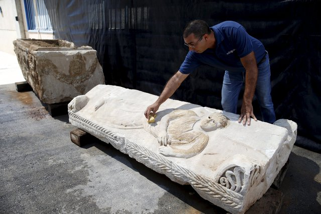 An employee of the Israel Antiquities Authority cleans an engraving on a sarcophagus as it is  displayed for the media near the Israeli town of Beit Shemesh September 3, 2015. The Israel Antiquities Authority (IAA) said on Wednesday that their inspectors and Israeli policemen have revealed the rare sarcophagus after it was concealed by contractors, who damaged it when they incorrectly removed it from the ground and hid it during construction work in the southern city of Ashkelon. (Photo by Baz Ratner/Reuters)