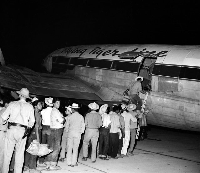 A group of illegal Mexican migrant workers are seen as they board a Flying Tiger airliner at Holtville, near El Centro, Calif., August 11, 1951, to be deported to their homes, some 1200 miles south of the U.S. border. Three planes, each carrying 60 deportees, leave at night so they will arrive at their destination at daybreak. U.S. immigration service inaugurated this system of air deportation early in June this year, with planes contracted by the U.S. Immigration Service commercial organization. (Photo by AP Photo)
