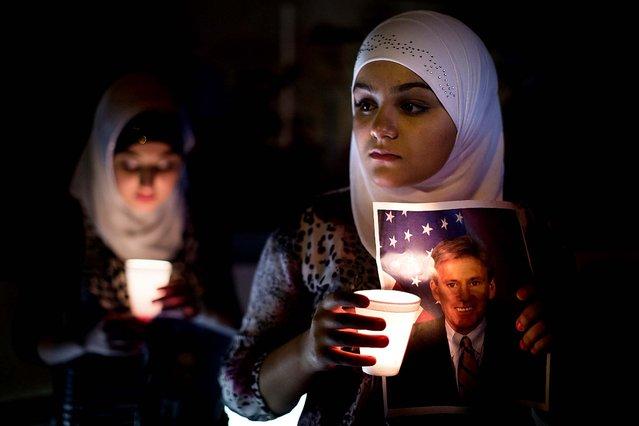 Dilan Samo, 13, holds a picture of slain U.S. ambassador to Libya Christopher Stevens during a candlelight vigil outside the Libyan Embassy in New York. (Photo by John Minchillo/Associated Press)