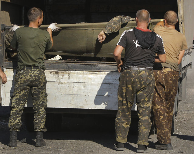Ukrainian army personnel load the body of a dead government soldier into a truck in the rebel-held town of Starobesheve, eastern Ukraine, Saturday, August 30, 2014. Ukrainian government forces have succumbed to a sequence of military failures and seen their holdings in the conflict-ridden east shrink in recent days as Russian-backed rebels continue their fast-paced offensive. (Photo by Sergei Grits/AP Photo)