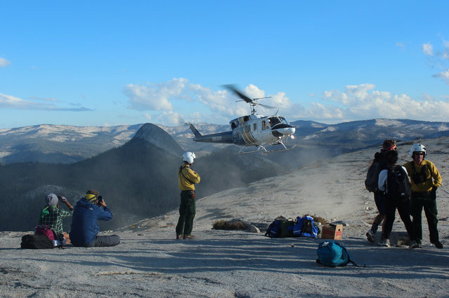 In this Sunday, September 7, 2014 photo provided by Rachel Kirk, hikers are evacuated from Yosemite National Park, Calif. About 100 Yosemite National Park visitors were evacuated from the top of Half Dome by helicopter Sunday when a wildfire that started weeks ago in the park's backcountry grew unexpectedly to at least 700 acres, officials said. (Photo by Rachel Kirk/AP Photo)