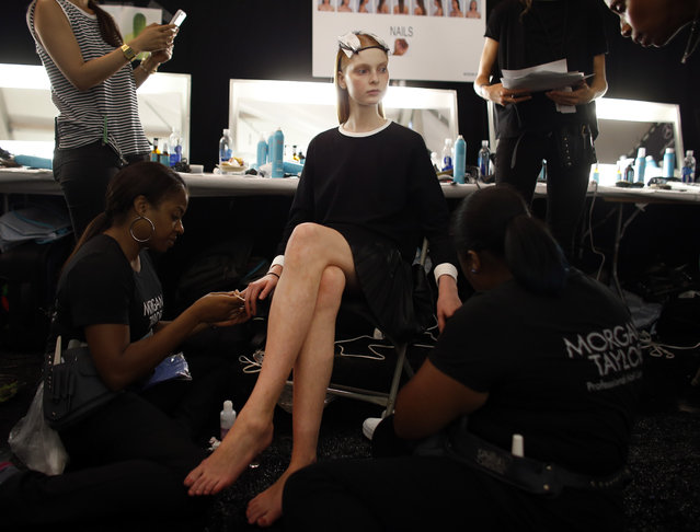 Fashion model Dasha Jold, 18, of Yekaterinburg, Russia, has her nails done backstage before the Monique Lhuillier Spring 2015 collection show Friday, September 5, 2014, during Fashion Week in New York. Jold was scouted on the street in her native Russia, at age 17. She struggles sometimes with homesickness, but says that keeping in touch through services like Skype helps ease those feelings. (Photo by Jason DeCrow/AP Photo)