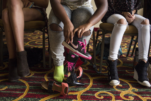 Tiana Pindell, 15, of Baltimore Md., puts on her sneakers after walking in heels for runway practice at a modeling camp at the Courtyard Marriott Hotel in McLean, Va., on Tuesday, August 18th, 2015. (Photo by Brittany Greeson/The Washington Post)