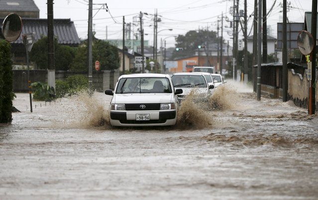 Cars travel through a residential area flooded by the Kinugawa river, caused by typhoon Etau, in Joso, Ibaraki prefecture, Japan, September 10, 2015. (Photo by Issei Kato/Reuters)