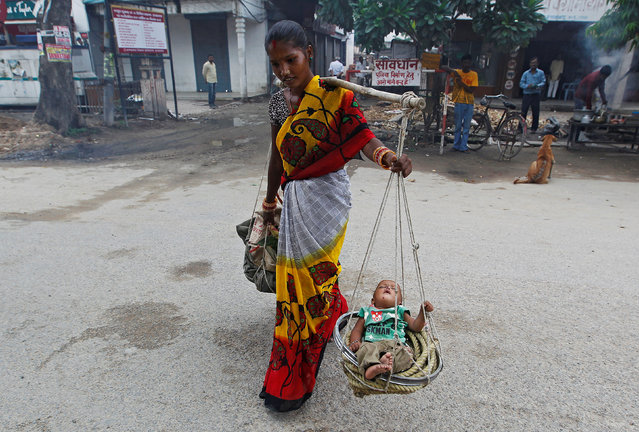 A woman carries her child in a basket as she walks on a road in Allahabad, India, August 11, 2016. (Photo by Jitendra Prakash/Reuters)