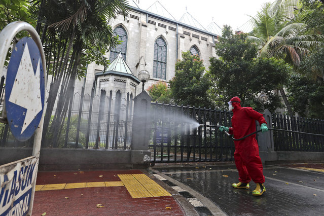 A fireman sprays disinfectant in an attempt to help curb the spread of the new coronavirus outbreak outside the cathedral in Jakarta, Indonesia, Wednesday, June 3, 2020. (Photo by Achmad Ibrahim/AP Photo)