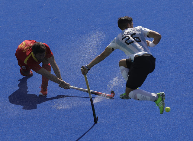 Argentina's Agustin Mazzilli, right, fight for the ball with Spain's Miguel Delas, left, during a men's field hockey quarterfinal match at 2016 Summer Olympics in Rio de Janeiro, Brazil, Sunday, August 14, 2016. (Photo by Hussein Malla/AP Photo)