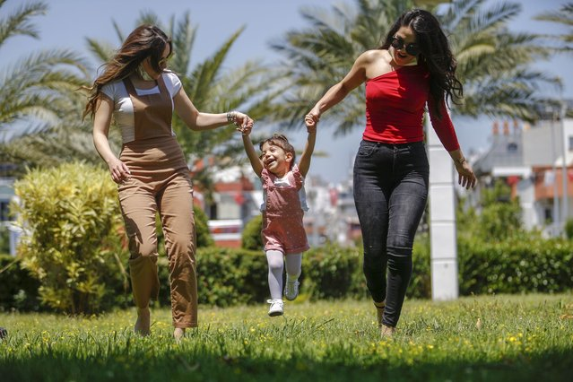 A kid enjoys with her family at a park after children under 14 years across Turkey allowed to leave their homes, remaining within walking distance and wearing masks, on May 13 between 11 a.m. and 3 p.m. local time, in Antalya, Turkey on May 13, 2020. Turkey on Wednesday eased coronavirus (Covid-19) restrictions for young people under 14 years old. (Photo by Mustafa Ciftci/Anadolu Agency via Getty Images)
