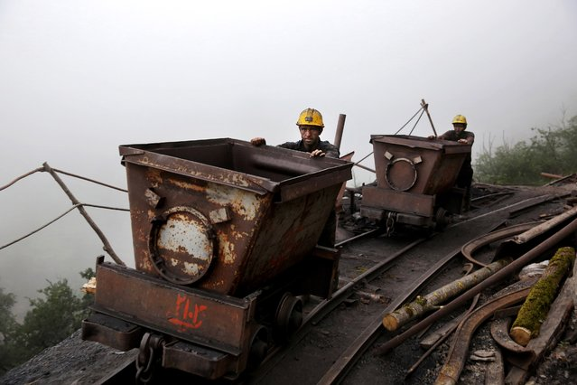 In this Thursday, May 8, 2014 photo, Iranian coal miners push metal carts to be loaded with coal at a mine near the city of Zirab 212 kilometers (132 miles) northeast of the capital Tehran, on a mountain in Mazandaran province, Iran. International sanctions linked to the decade-long dispute over Iran's nuclear program have hindered the import of heavy machinery and modern technology in all sectors, and coal mining is no exception. (Photo by Ebrahim Noroozi/AP Photo)