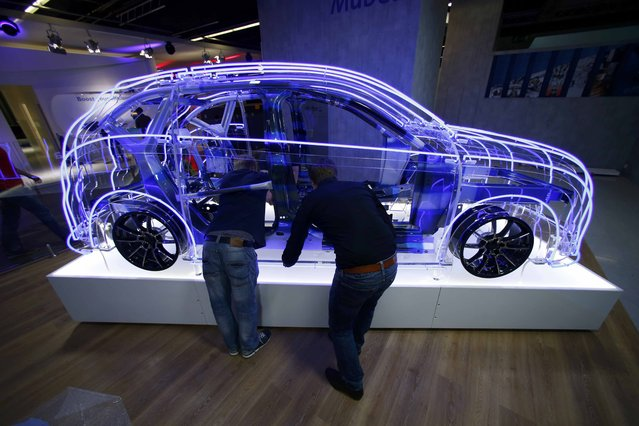 Employees work at the booth of Mubea company during the media day at the Frankfurt Motor Show (IAA) in Frankfurt, Germany, September 14, 2015. (Photo by Ralph Orlowski/Reuters)