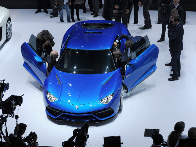 Visitors look at Lamborghini Asterion cars at the Lamborghini stand at the Paris Auto Show on October 2, 2014 on the first of the two press days. (Photo by Eric Piermont/AFP Photo)