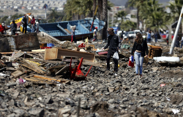 People walk through debris left behind by an earthquake-triggered tsunami in the coastal town of Coquimbo, Chile, Thursday, September 17, 2015. Several coastal towns were flooded from small tsunami waves set off by late Wednesday's quake, which shook the Earth so strongly that rumbles were felt across South America. (Photo by Luis Hidalgo/AP Photo)