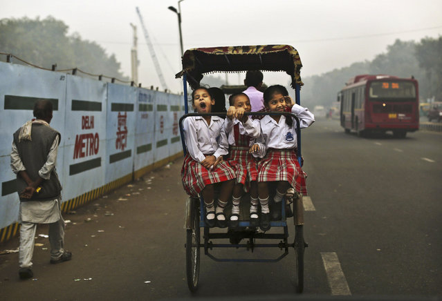 A girl yawns as she rides with friends to school on a bicycle rickshaw in New Delhi, India, October 31, 2012. (Photo by Kevin Frayer/Associated Press)