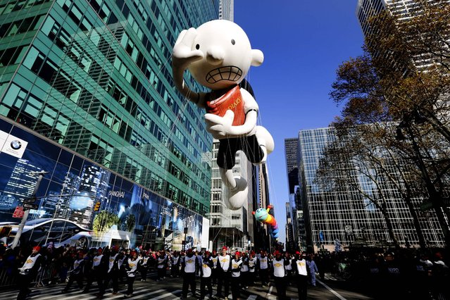 The Diary of A Wimpy Kid balloon and its wranglers travel down the Avenue of the Americas during the 86th annual Macy's Thanksgiving Day Parade. (Photo by Librado Romero/The New York Times)
