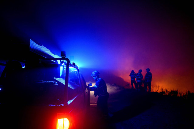 Firefighters gather to evaluate the progression of the wildfire at Calheta in Madeira island on August 12, 2016. Firefighters were making progress in quenching forest fires that have ravaged parts of Portugal and France, officials said on August 12, 2016, as Spain faced a rash of possibly deliberate blazes. The situation had calmed down on the frontline of fires in northern Portugal and on the island of Madeira where three people perished this week in the flames. (Photo by Patricia de Melo Moreira/AFP Photo)