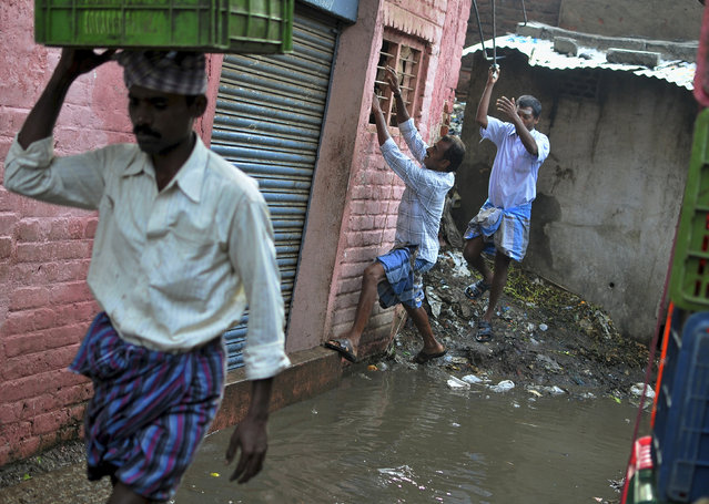 A man holds onto a window grill as he attempts to cross a waterlogged footpath at a market in the southern Indian city of Bangalore October 9, 2014. (Photo by Abhishek N. Chinnappa/Reuters)