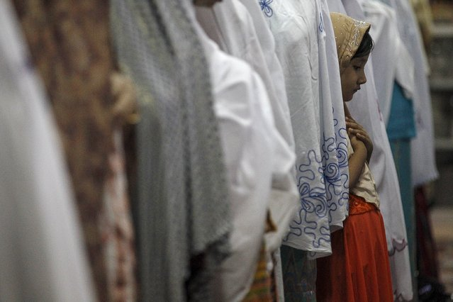 A Muslim girl stands while performing the Eid al-Adha prayer at a mosque in Yangon, Myanmar September 25, 2015. (Photo by Soe Zeya Tun/Reuters)