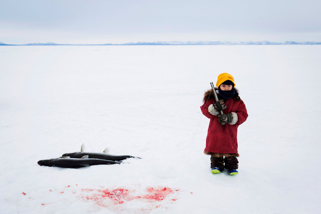 """A selection of work by five photojournalists who have won grants of $10,000 and editorial support from the agency. Here: """"Chasing Winter"""" by Katie Orlinksy. Orlinsky's project examines the effects of climate change in Alaska. Here, a girl catches sheefish from an ice hole on the frozen Kotzebue Sound. (Photo by Katie Orlinsky/Getty Images)"""