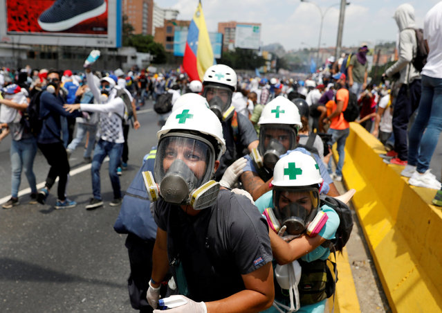 Volunteer members of a primary care response team, huddle together during clashes with security forces at a rally against Venezuela's President Nicolas Maduro in Caracas, Venezuela, April 26, 2017. In Caracas, around 120 medicine students, doctors, and volunteers have revived a primary care response team first created during 2014's bout of anti-government protests. While they wear white helmets with a green cross, none wear flak jackets and some resort to wearing goggles to protect themselves from tear gas. Their equipment has nearly all been donated or bought by the volunteers themselves, and they've had to create makeshift neck braces from shoes, belts, and hats. (Photo by Carlos Garcia Rawlins/Reuters)