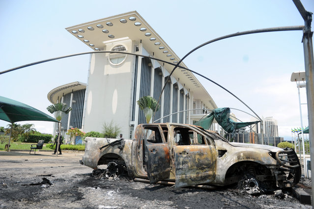 Burnt out cars are seen outside a government building, following an election protest in Libreville, Gabon, Thursday September 1, 2016. Gabon's newly re-elected president sought to assert authority Thursday as the presidential guard attacked the opposition candidate's party headquarters overnight, killing at least one person and injuring more than a dozen amid fiery protests that have seen hundreds detained and the internet blocked. (Photo by Joel Bouopda/AP Photo)